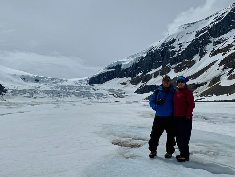 An image of a couple hiking on the Athabasca Glacier in Jasper National Park in Alberta, Canada.