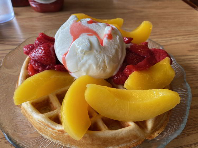 An image of a waffle with ice cream, peaches and strawberries.